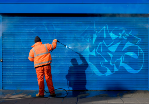 Graffiti removal services, worker removing graffiti from blue building